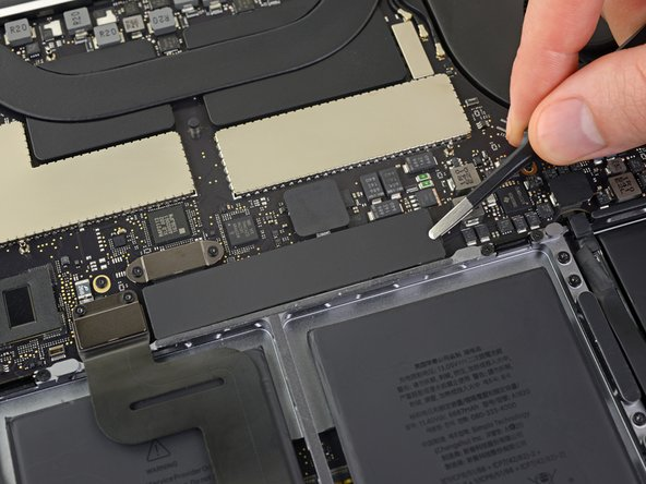 Peel up and remove the large rectangular battery board cover, on the edge of the logic board nearest the battery.