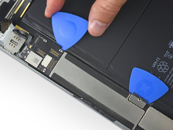 Insert an opening pick underneath  the logic board at the corner of the large EMI shield.