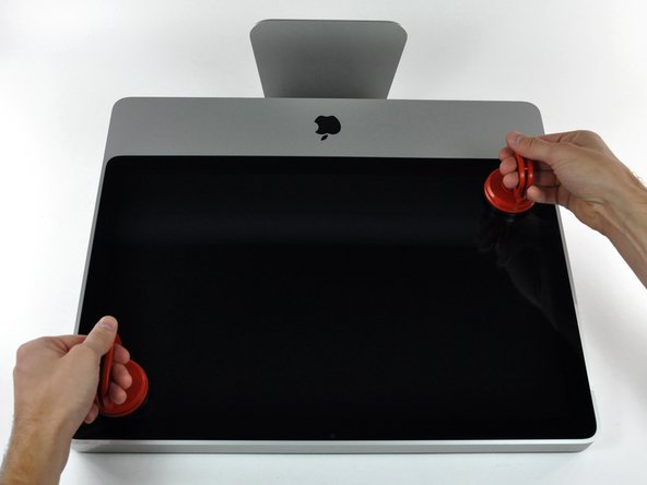 Gently pull the glass panel straight up off the iMac.