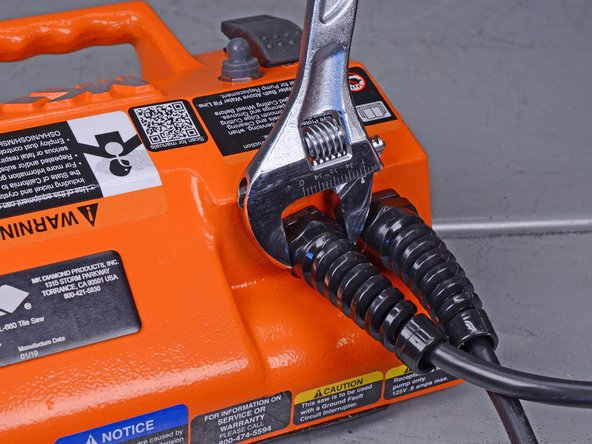 Use an adjustable wrench to loosen the hex nut closest to the wall plug side of the power cord.