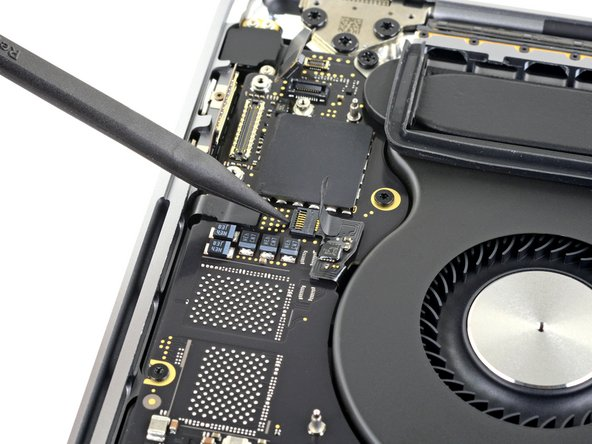 Open the locking flap on the left fan's ZIF connector by prying it straight up from the logic board.
