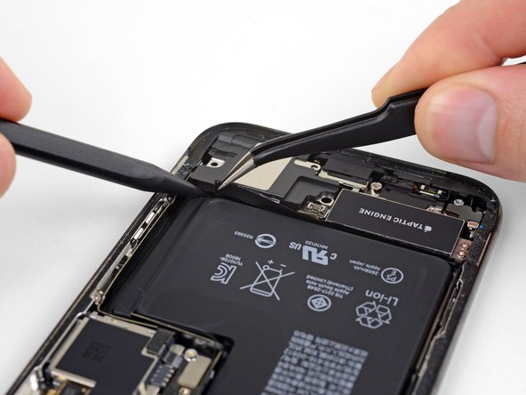 While prying up the speaker, use tweezers to peel away the plastic bumper strip from the top edge of the speaker.