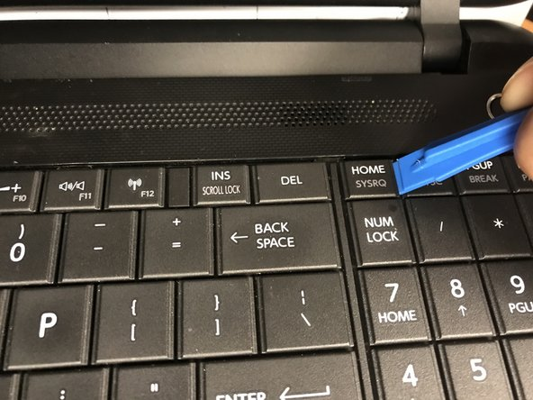 Use a plastic opening tool to lift a key off of the keyboard