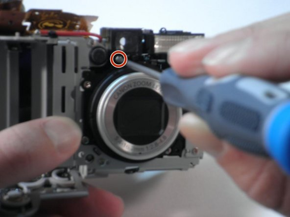 Remove the final screw directly under the left side of the viewfinder (on the lens side) with a Phillips #00 screwdriver.