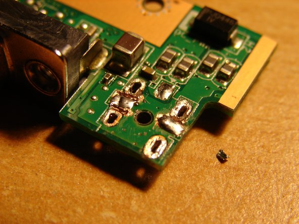 Congrats! You have successfully removed the old charging plug. Now, put some new solder onto the cleaned solder joints - but just a bit, not too much! Pay attention that the openings of each solder joint of the charging plug remain open!