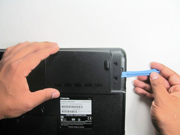 Using a flat head from a plastic opening tool to lift open the cover.