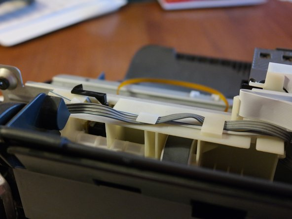 The stepper motor cable is routed through a series of plastic tabs that hold it down.