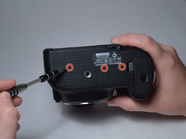 Remove the three 3.5-mm  screws from the underside of the camera that are circled.