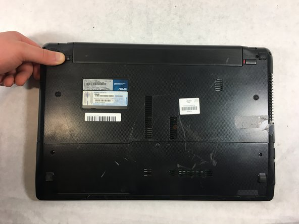 Slide the other sliding lock on the left side of the battery to the left, and with your other hand slide the battery out from the laptop.