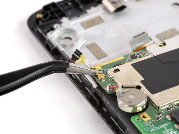 Use a pair of tweezers to pry up and disconnect the antenna cable from the back of the motherboard.