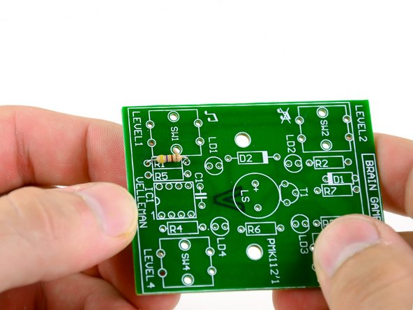 Place the leads of the resistor through the holes on either side of the rectangle marked R1 on the circuit board.