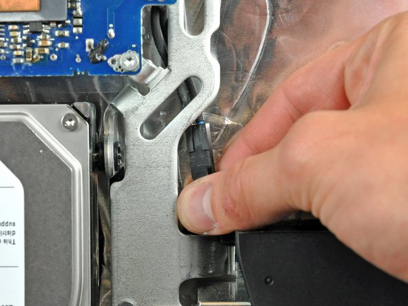 Disconnect the AC-In cable by depressing the lock mechanism while pulling the connector away from its socket.