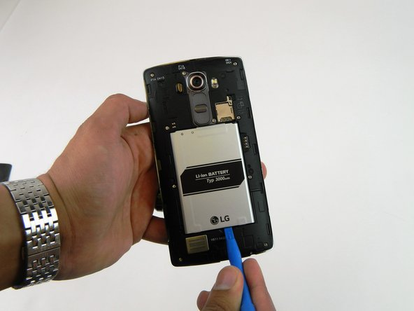 Place the plastic opening tool at the bottom edge of the battery and lift up.  Carefully remove battery with your hands.