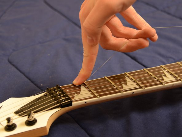 Using one finger of one hand, press down lightly onto the first fret of the string you are changing. Use the remaining fingers to lift up the string. This will ensure that there is slack on the string to use when winding it later.