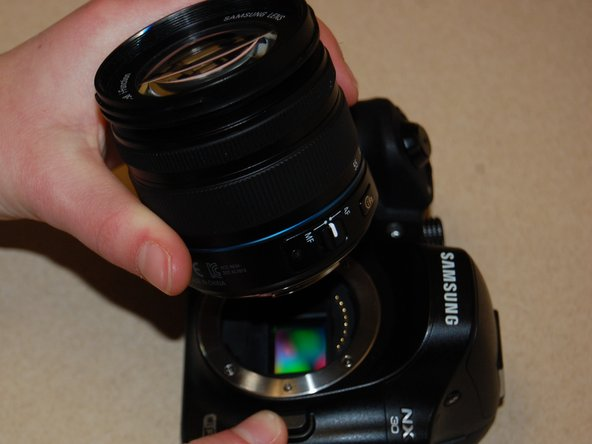 While holding the lens release button, grasp the lens from the base.