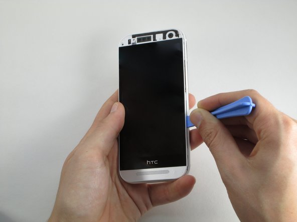 Use the plastic pry tool to pry around the edge of the phone.