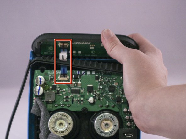 Lift up the retaining flap on the button cable ZIF connector.