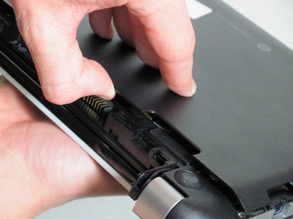 Wedge your finger (or tool) in between the outer plastic cover of the laptop and the main part of the laptop.