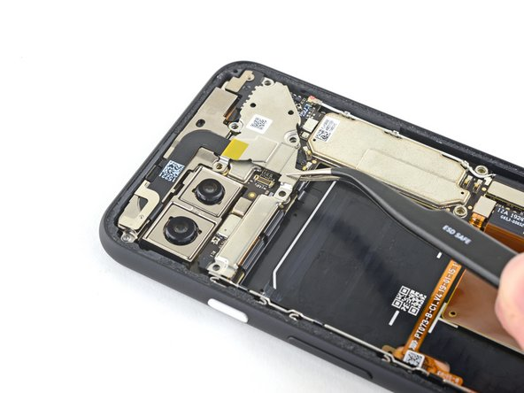 Using a pair of tweezers, tilt the camera cover up and slide it out of the retaining slot on the upper right corner of the phone to remove.