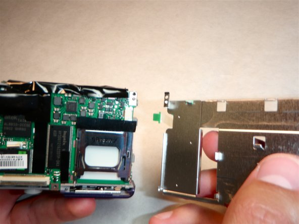 Remove the ribbon cable from its slot by gently pulling the LCD holding plate to the right.