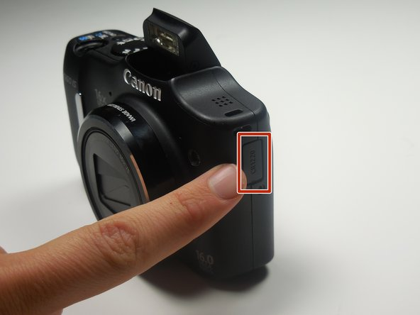 Locate the internal battery tray on the side of your camera.