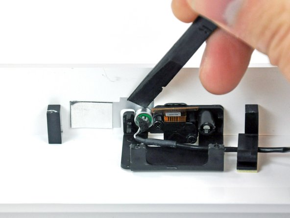 Use the flat end of a spudger to pry the microphone off the adhesive holding it to the front bezel.