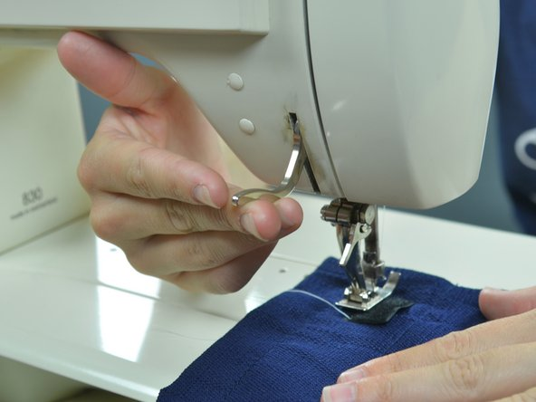 Lift the presser foot, leaving the needle sunk.