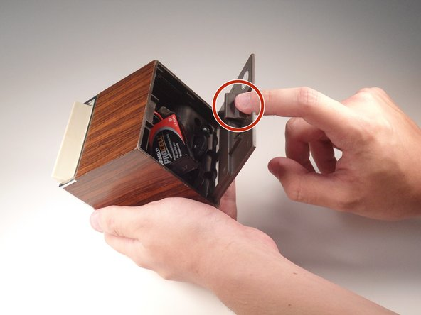 To remove the back panel from the Weather radio, use your index finger and push down on the tab located on the back.