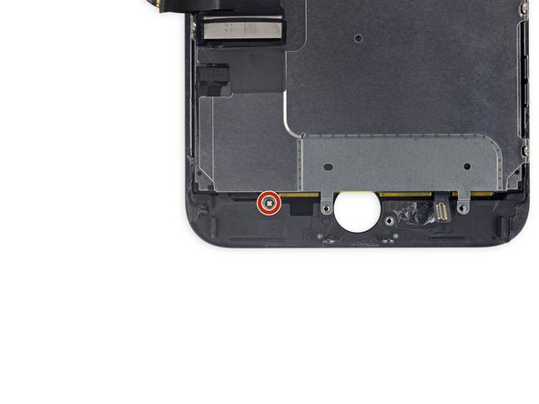 Remove the 1.8 mm Phillips screw securing the EMI shield near the bottom of the display.