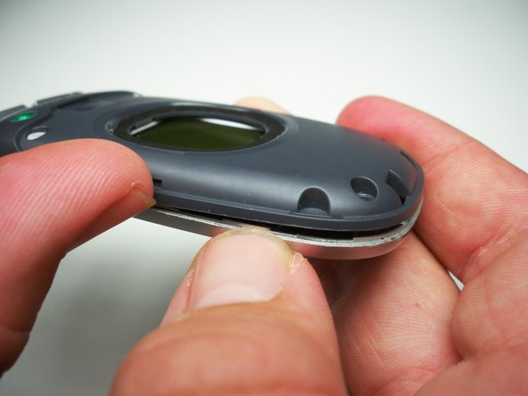 Pry up the dark grey case with your fingernail until all four snaps around the top are loose.