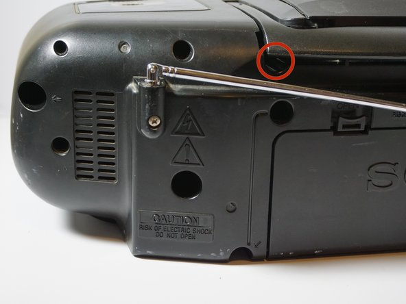 Hold the boombox handle at an angle to access the screws behind the CD player.