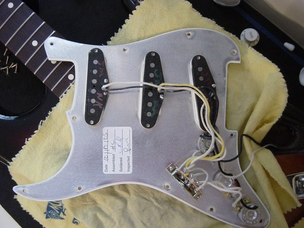 Another method of dis-assembly: remove the pickguard screws (leaving pickup screws, pots and switch untouched).