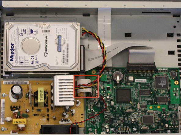 Carefully remove the ribbon cable from the power supply. Hold the ribbon on both sides and pull up.