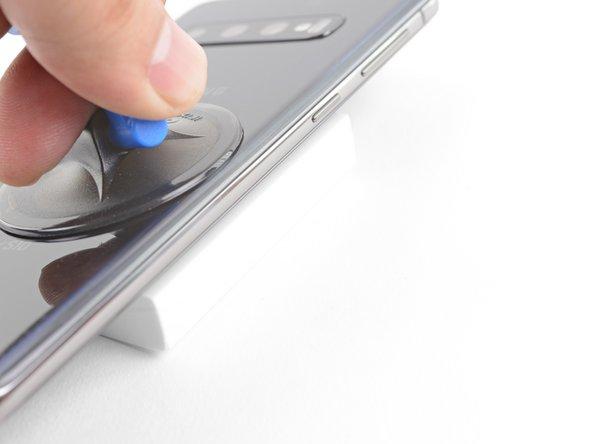 Posa il lato destro riscaldato del telefono su qualcosa che abbia uno spessore di 10-15 mm. Si crea così un angolo sufficiente per poter usare lo strumento di apertura.