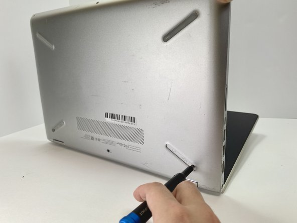 Push into the two screw holes that were under the rubber pads with the screwdriver to pop the keyboard out just a little.
