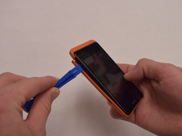 Insert the plastic opening tool into the seam between the front of the device and the rear cover.
