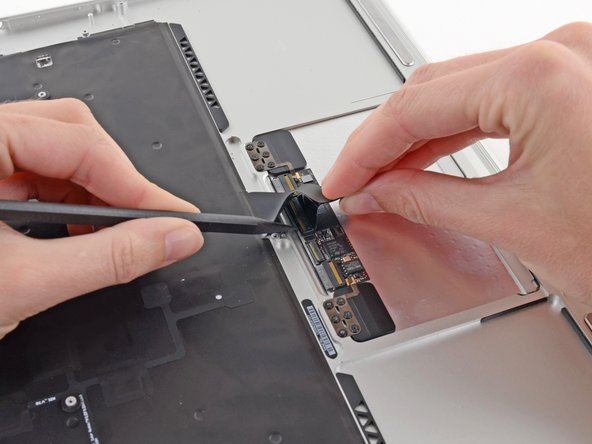 While carefully lifting the keyboard ribbon cable with one hand, use the tip of a spudger or your fingernail to flip up the retaining flap on the keyboard ribbon cable ZIF socket.