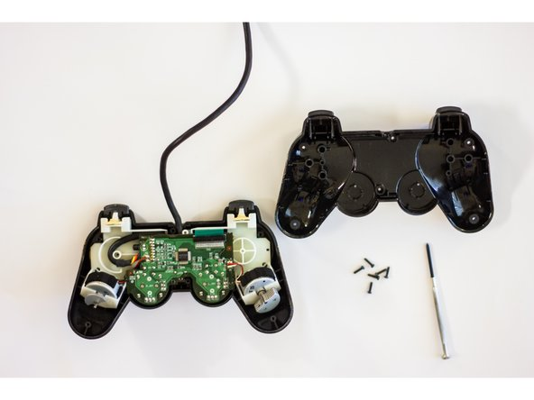 Once the screws are removed, carefully pry the controller open with your hands.