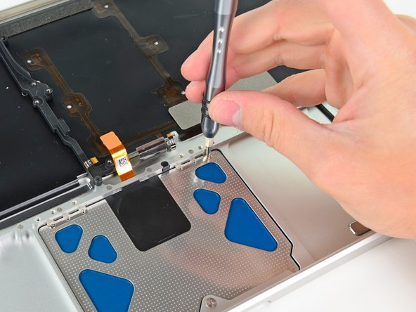 Insert a 1.4 mm Y0 Tri-wing screw into each of the outer holes drilled into the trackpad (two screws total).