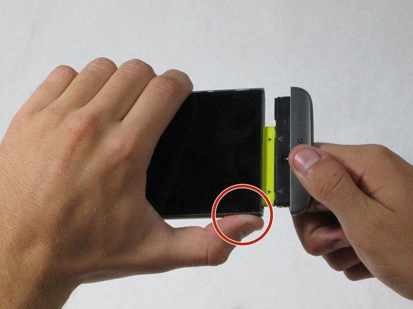 While holding the battery release button, pull the bottom end of the phone out of the body.