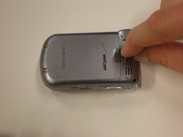 Retirez la batterie en pinçant et déverrouillant le clip situé au-dessus du logo Verizon à l'arrière du téléphone.