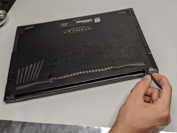 After the screws are removed, carefully insert a plastic spudger in the space between the backplate and the rim of the laptop.