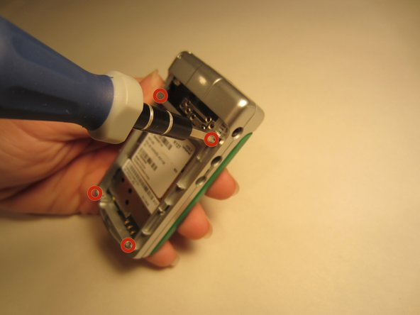 Use the Y1 tri-wing screwdriver to remove the four 2.4mm screws and then pry the entire backing off of the phone including the black clip attached to the top of the motherboard.