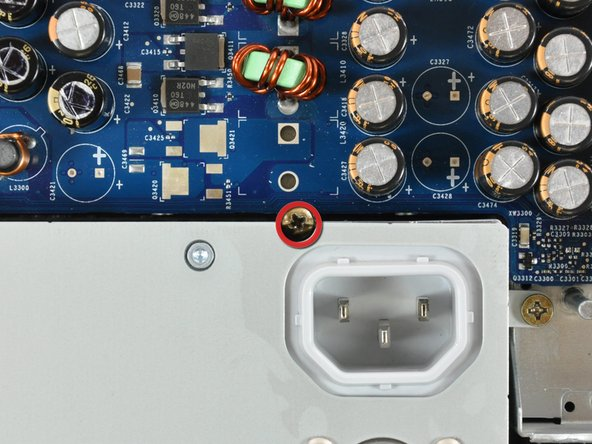 Loosen the center Phillips screw securing the power supply to the front case.