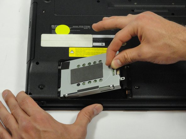 While still holding the plastic tab, lift the right side of the hard drive out at a 45º angle.