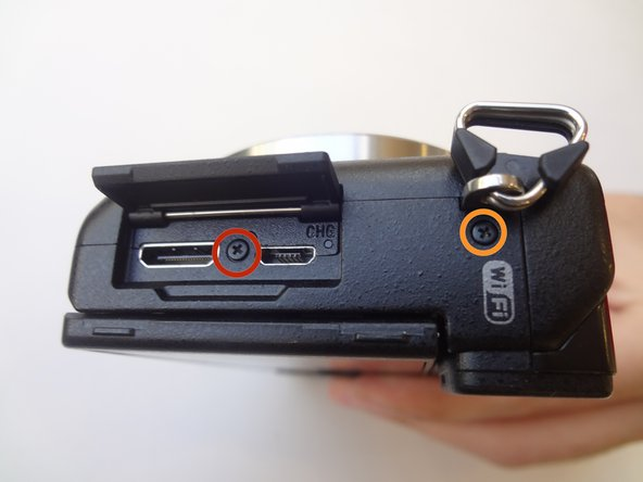 Remove the 3.5 mm Phillips #00 screw on the side of camera - located between the charging and HDMI ports.