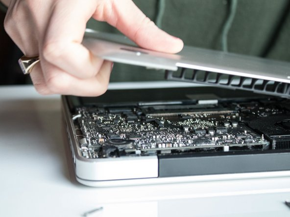 Lift back cover off of your MacBook Pro and set aside. It might make a loud sound and that is okay.