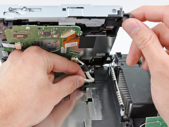 Lift the side of the DVD drive opposite the controller ports enough to access the cables on its bottom face.