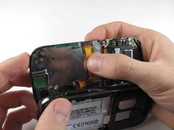 Press your thumb against the orange power cable and pull it down slowly to disconnect the power cable from the bottom of the keyboard.