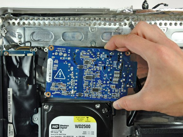 Lift the power supply out of the rear case, minding the AC-in cable that may get caught.